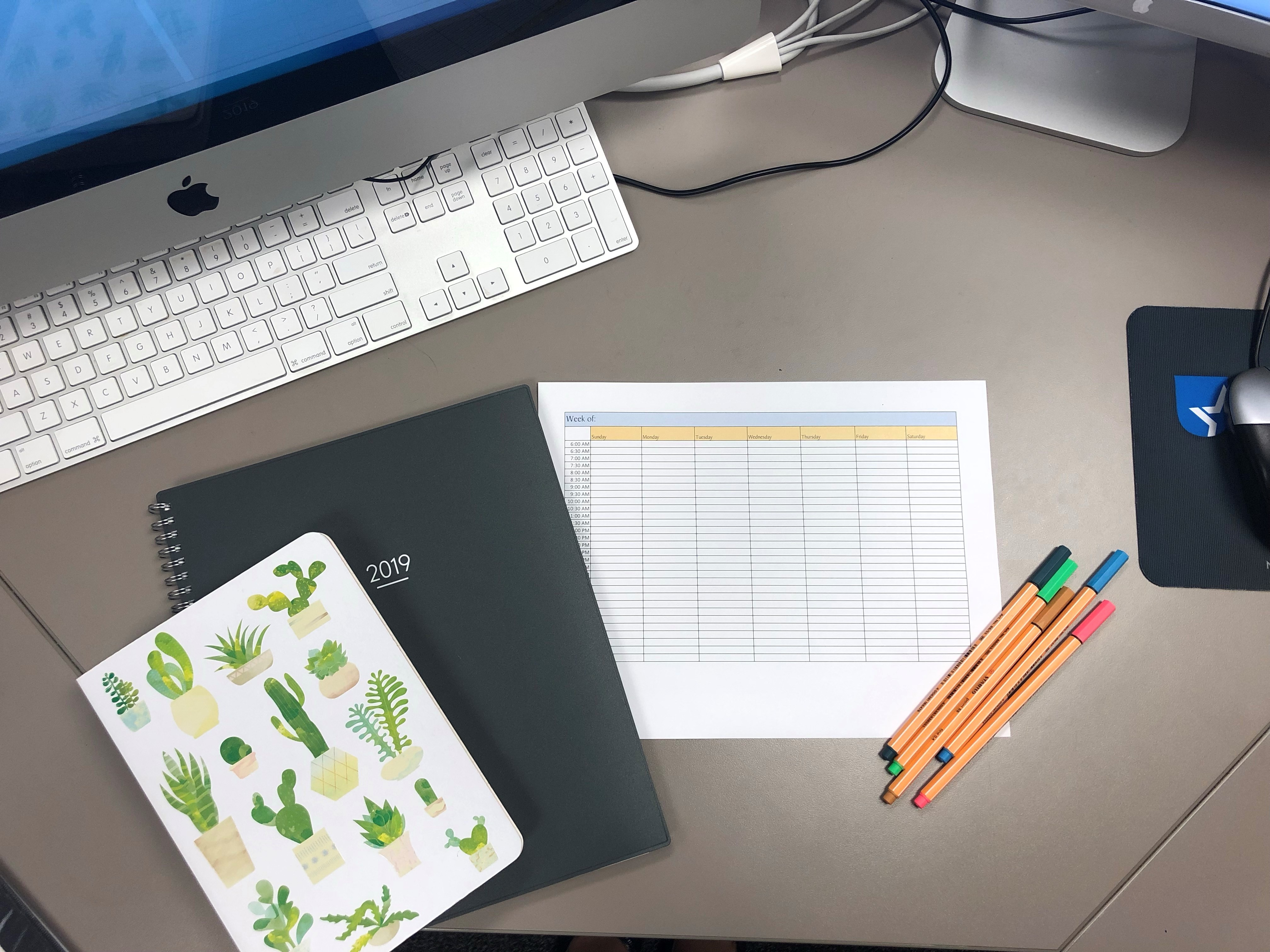 This picture shows an example of what it may look like when you sit down and get organized. There are colored pens for color coordination, a time blocking template, a 2019 planner, and a notebook for a to-do list. Time blocked schedules can make you a more productive and effective professional or student.