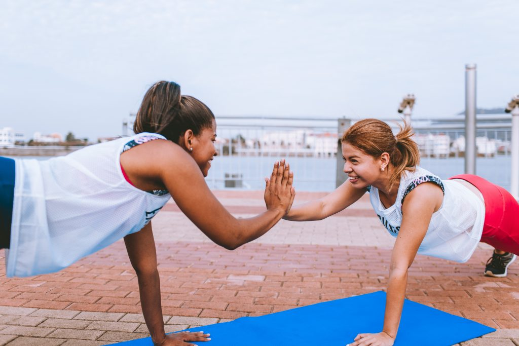 Two friends working out and forming healthy habits. It emphasizes the importance of having a support system to hold yourself accountable to new, healthy habits.