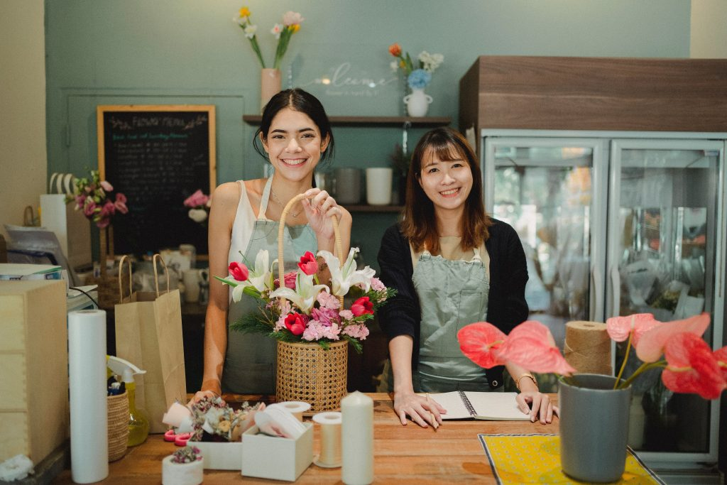 Two women in a florist shop smiling at the camera. Chose this picture to represent small business owners and managers.